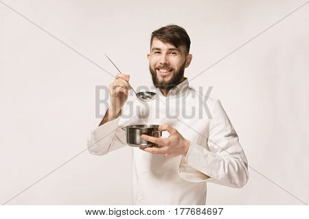 Aroma of a dish. Head chef smelling the food standing against white background. Chef smelling the aroma of a dish.