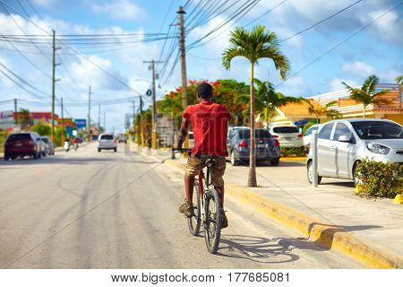 BAVARO DOMINICAN REPUBLIC - 09.01.2015: Undefined man riding on bicycle along the Bavaro city road