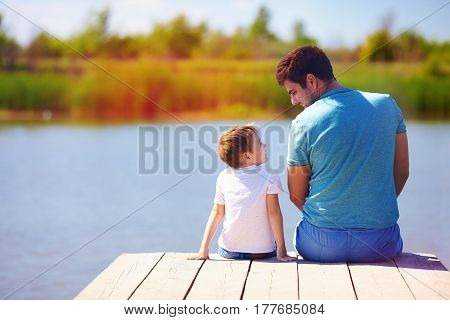 Father And Son Sitting On Pier By The Lake On Sunny Summer Day