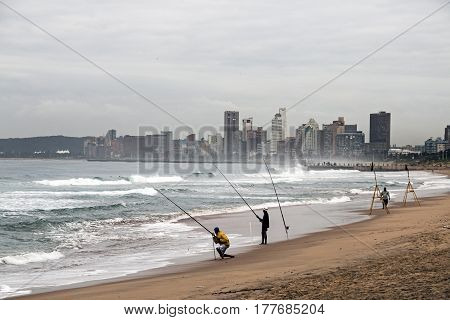 Unknown Fishermen On Beach Against Overcast Durban City Skyline