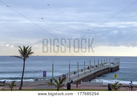 Early Morning Visitors On Beachfront And Pier Against Skyline