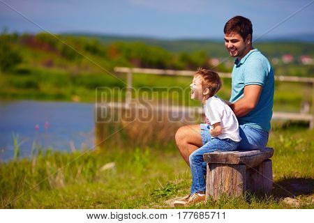 Father And Son Having Fun, Sitting On The Bench By The Lake On Sunny Summer Day