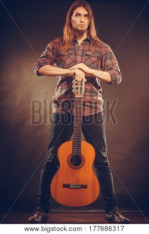 Music hobby concept. Young man is standing and holding his guitar. Artist is exposing the instrument.