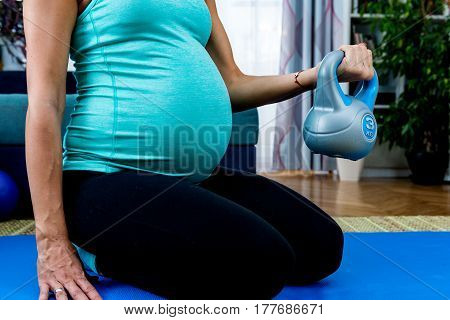 Young pregnant woman exercising at home. color image