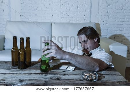 wasted alcoholic and drug addict man with loose tie snorting cocaine and drinking beer bottles at home living room couch in toxic substance addiction and abuse concept