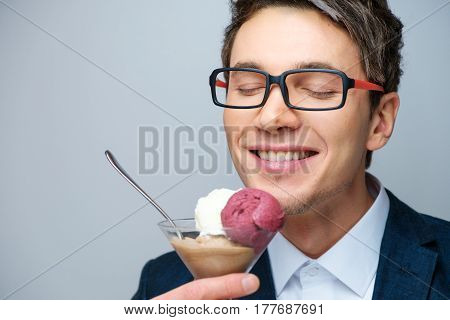 Handsome young man with glasses, a blue jacket and white shirt with multi-colored ice-cream balls in a transparent cup and teaspoon in the studio