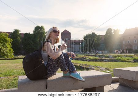 Female traveler sitting and enjoys the view of Wawel Castle with a bottle of water in the rays of sunlight. Krakow, Poland