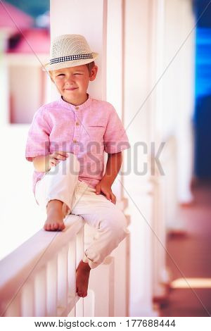 Cute Smiling Kid Sitting In Shadows On Summer Caribbean Street