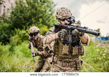 Two military man snipers with airsoft automatic rifle with a telescopic sight lies in grass in forest. Focus on rifle of first man