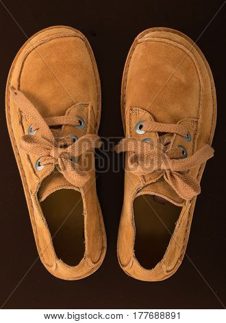 Pair of fashion stylish chamois leather shoes for women isolated on a black background close up top view.