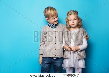 Beautiful little princess and handsome boy. Friendship. Love. Valentine. Studio portrait over blue background