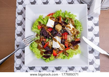 Fresh vegetable salad with cheese on a white plate with cutlery Salt and pepper. Greek vegetable salad with feta cheese