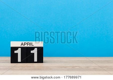 April 11th. Day 11 of month, calendar on wooden table and blue background. Spring time, empty space for text.