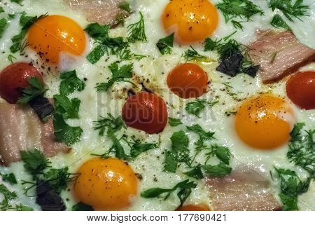 Tasty and nutritious eggs fried in a skillet with bacon tomatoes dill and parsley.