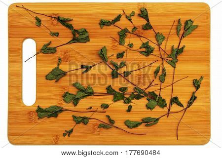 The dried herb mint lying on a cutting board made of bamboo on a white background.