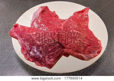 Juicy red raw beef lying on a white plate.