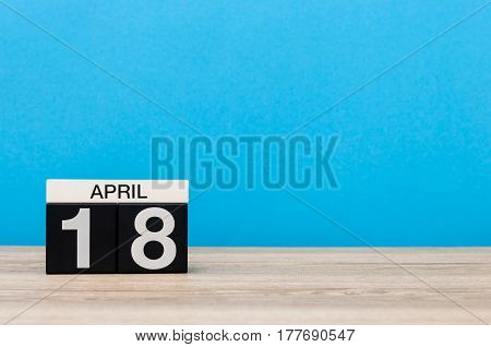April 18st. Day 18 of month, calendar on wooden table and blue background. Spring time, empty space for text.
