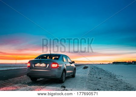 Gomel, Belarus - January 26, 2017: Volkswagen Polo Car Sedan Parking On A Snowy Roadside Of Country Road On A Background Of Dramatic Sunset Sky At Winter Season