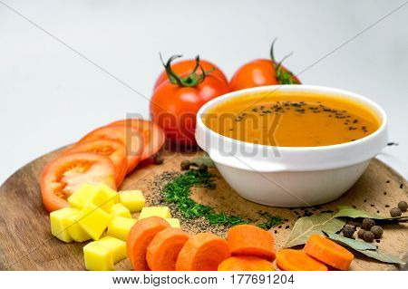 Vegetable soup surrounded by fresh vegetables. close up