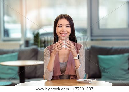 Coffeebreak in cozy cafe. Beautiful brunette with smartwatch having cup of coffee. Nice coffee house interior. Big window as a background. Woman looking at camera and smiling