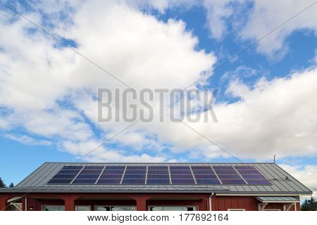 Solar Panels for generating eco-friendly electricity on the rooftop of house against white clouds and blue sky