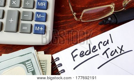 Federal tax written in a notebook and calculator.