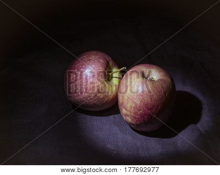 Pair of Pink Lady apples darkness illuminated by un LED light beam.