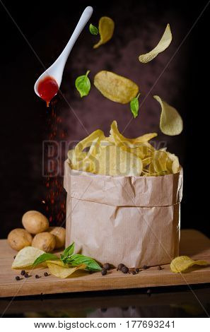 Potato chips flying over a bowl .