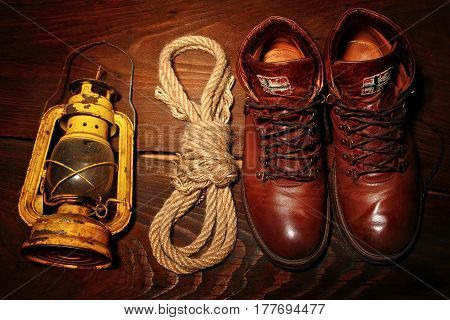 Travel boots old latern kerosine lamp and sailor rope on wooden background.Top view