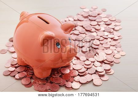 Piggy bank on pile of copper euro cents coins