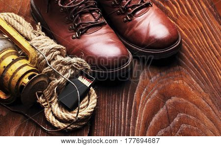Travel boots old latern kerosine lamp box of matches and sailor rope on wooden background.Copy space