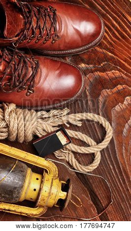 Travel boots old latern kerosine lamp box of matches and sailor rope on wooden background.Top view.Copy space