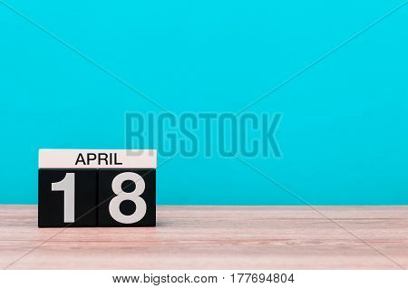 April 18st. Day 18 of month, calendar on wooden table and turquoise background. Spring time, empty space for text.