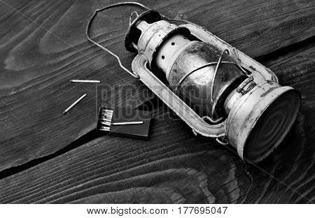 The old kerosene lantern laying with scattered maatches on the wooden table.copy space.Black and white