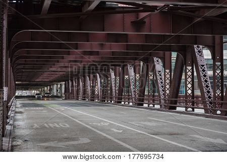 Side view cars driving on wide bridge. Bridge covering with iron roof, United States
