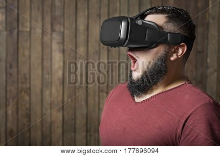 Bearded man with virtual reality glasses standing on the wooden background. concept of terrible, frightening virtual life