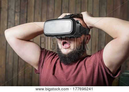 Bearded man with virtual reality glasses standing on the wooden background. concept of terrible, frightening, fear, phobia