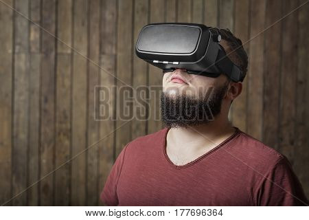 Bearded man with virtual reality glasses standing over wooden background. concept of nosy, curiosity, cognition, study, learning, scrutiny