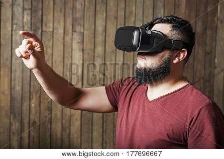 Bearded guy with virtual reality glasses standing over wooden background. concept of nosy, curiosity, cognition, study, learning