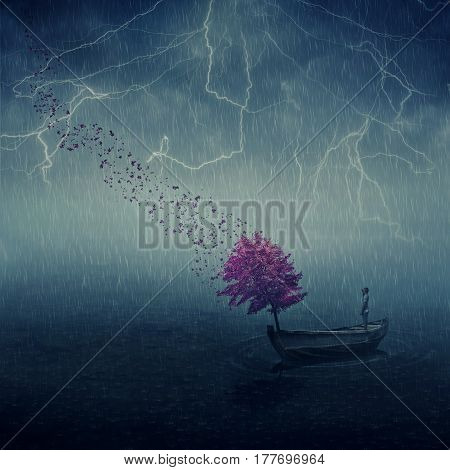 Surrealistic image as lonely boy floating in a wooden boat with a purple tree that cast its leaves in the wind. Lost in the middle of the sea below the falling rain journey and discovery.