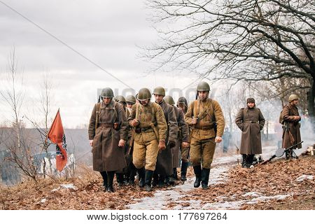Rogachev, Belarus - February 25, 2017: Group Of Re-enactors Dressed As Soviet Russian Red Army Infantry Soldiers Of World War II Marching Along Forest Road At Late Winter Season.