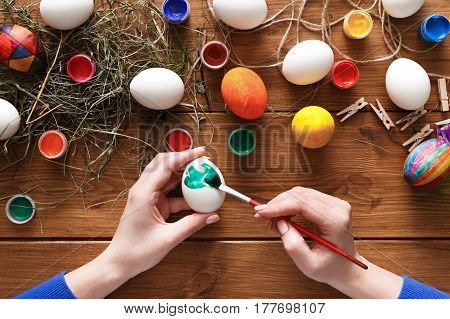 Paint easter eggs craft background. Top view on rustic wood with hay