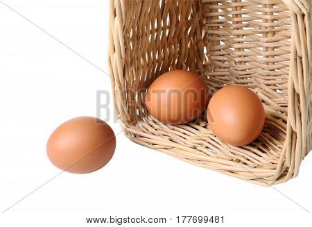 Three eggs in a basket closeup isolated on white