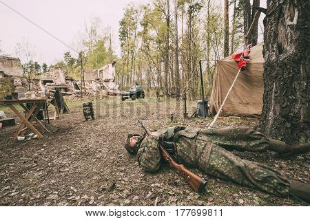 Pribor, Belarus - April 24, 2016: Re-enactor Dressed As German Wehrmacht Infantry Soldier In World War II Soldier Falling Down Dead On Battlefield In Forest Camp At Historical Reconstruction
