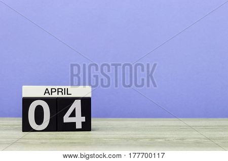 April 4th. Day 4 of month, calendar on wooden table and purple background. Spring time, empty space for text.