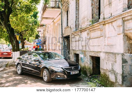 Batumi, Adjara, Georgia - May 25, 2016: Parked Black Volkswagen Passat CC Car Along Pavement Of Street With Old Buildings In Summer Day.