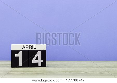 April 14th. Day 14 of month, calendar on wooden table and purple background. Spring time, empty space for text.