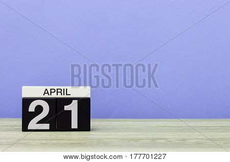 April 21st. Day 21 of month, calendar on wooden table and purple background. Spring time, empty space for text.