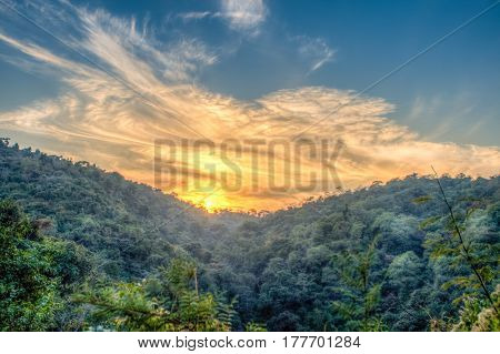 Mountain forest landscape under evening sky with clouds in sunlight. Majestic sunset in indian Himalaya mountains. HDR image.