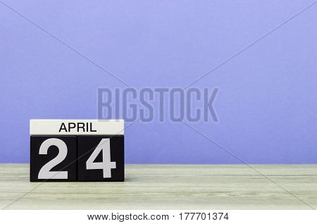 April 24th. Day 24 of month, calendar on wooden table and purple background. Spring time, empty space for text.